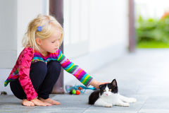Pretty girl patting a cat outside. Little pretty blond girl patting a cat outside on a garden patio. Summer or spring. Caring. Child connecting with a pet cat Royalty Free Stock Photos