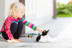 Pretty girl patting a cat outside. Little pretty blond girl patting a cat outside on a garden patio. Summer or spring. Caring. Child connecting with a pet cat Stock Photo