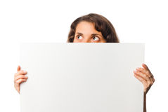 Pretty girl peeps out from behind the blank board Stock Photos