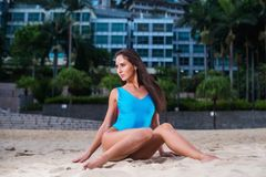 Pretty girl with perfect body dressed in blue swimsuit sitting on beach against hotel enjoying and dreaming.  Stock Images