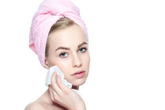 Pretty girl with perfect complexion cleansing her face using soft face wipe . Isolated on white background with copy space. Attractive young blond woman with royalty free stock photos