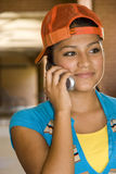 Pretty girl on phone. A pretty young Hispanic girl smiling and enjoying her conversation on her cell stock image