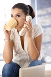 Pretty girl on phone drinking tea Royalty Free Stock Photos