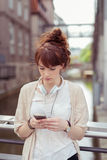 Pretty Girl with Phone Leaning Against Railings Stock Images