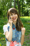Pretty girl with the phone smiling. In the park Stock Photography