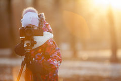 Pretty girl photographer taking pictures on camera using tripod, sunset light, winter, copyspace Stock Photo