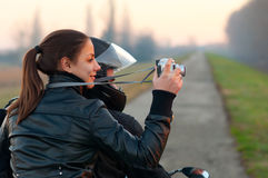 Pretty girl photographing nature from motorcycle. Beautiful teenage girl photographing nature from motorcycle on autumn day royalty free stock photo