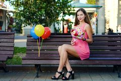 Pretty girl in pink dress with balloons and bouquet of flowers. Brown-haired woman sits in park on bench. concept holiday and gifts royalty free stock photography