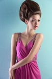Pretty girl in pink elegant dress. Fashion shot of a gorgeous brunette with a a fashion hair up-do and wearing an elegant pink evening dress with small pearls Stock Images