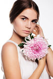 Pretty girl with pink flower near face Royalty Free Stock Photos