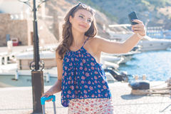 Pretty girl with pink suitcase taking selfie Royalty Free Stock Photos