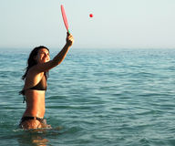 Pretty girl playing ball in the ocean Royalty Free Stock Image