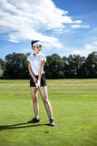 Pretty girl playing golf on grass. In summer Royalty Free Stock Images