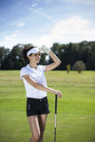 Pretty girl playing golf on grass. In summer Royalty Free Stock Image