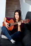 Pretty girl playing guitar on the couch Royalty Free Stock Photo