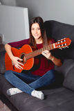 Pretty girl playing guitar on the couch Stock Photos