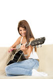 Pretty girl playing guitar on the sofa Stock Photos