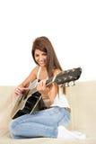 Pretty girl playing guitar on the sofa stock photos