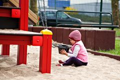Pretty girl playing in sandbox with pail Stock Images