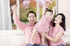 Pretty girl playing on sofa with parents Stock Image