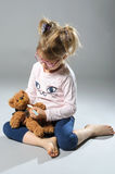 Pretty girl plays in the doctor treats a teddy bear on a gray ba Royalty Free Stock Photo
