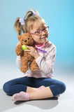 Pretty girl plays in the doctor treats a teddy bear on a gray ba Stock Images