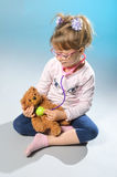 Pretty girl plays in the doctor treats a teddy bear on a gray ba Royalty Free Stock Image