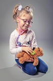 Pretty girl plays in the doctor treats a teddy bear on a gray ba Royalty Free Stock Images