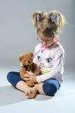 Pretty girl plays in the doctor treats a teddy bear on a gray ba Stock Photography