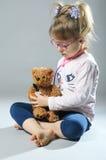 Pretty girl plays in the doctor treats a teddy bear on a gray ba Stock Photos