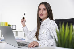 Pretty girl in a polka dot shirt smiling and holding a pen Stock Photos