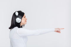 Pretty girl ponting finger aside with headphones Royalty Free Stock Photos