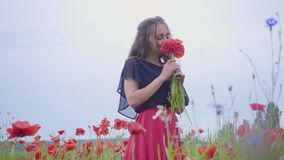 Pretty girl in a poppy field holding bouquet of flowers in hands, admiring beautiful flowers. Connection with nature. Pretty girl in poppy field holding bouquet stock video footage