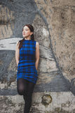 Pretty girl posing against a concrete wall Royalty Free Stock Photos