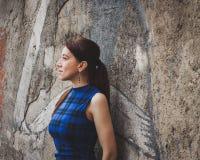 Pretty girl posing against a concrete wall Stock Photos
