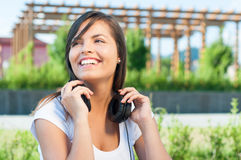 Pretty girl posing outside in park with headphones. Being happy with copy text space Stock Images