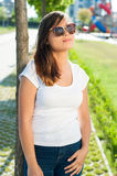 Pretty girl posing outside in park in sunlight Royalty Free Stock Photography