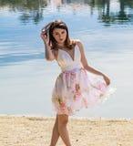 Pretty girl posing wearing flowering. Gorgeous fashion girl posing wearing flowering, with lake background Stock Photo
