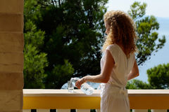 Pretty girl pours water Royalty Free Stock Photos
