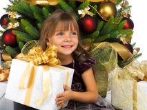 Pretty girl with present near the Christmas tree Stock Photo