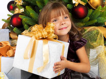 Pretty girl with present near the Cristmas tree Royalty Free Stock Photo