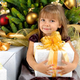 Pretty girl with present near the Cristmas tree Stock Photography