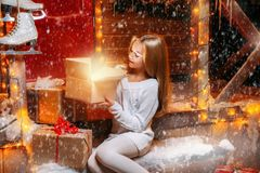 Pretty girl with presents. Pretty child girl sits on the porch of a house decorated for Christmas and opens a gift box and surprises. Time for miracles royalty free stock image