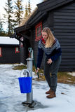 Pretty girl pumping a hand pump from a well Royalty Free Stock Photography