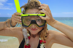 Pretty girl puts on snorkle and mask Royalty Free Stock Images