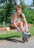 Pretty girl putting on inline skates. Royalty Free Stock Photo