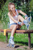 Pretty girl putting on inline skates. Royalty Free Stock Image