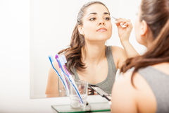 Pretty girl putting some makeup on. Beautiful young woman getting ready in the bathroom and putting on some makeup on her eyes Royalty Free Stock Image