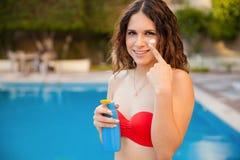 Pretty girl putting suntan on Royalty Free Stock Image