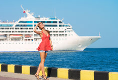 Pretty girl at the quay. Pretty girl walking along the quay and the ship sailing by Royalty Free Stock Images